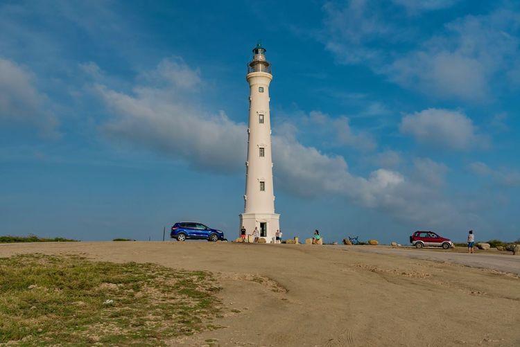 Lighthouse on beach against cloudy sky during sunny day