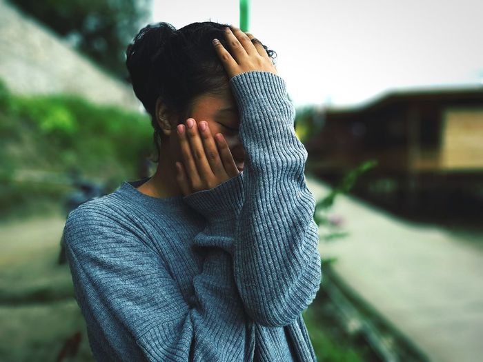 Close-up of young woman hiding face against clear sky