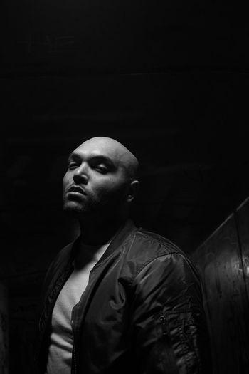 Portrait Of Bald Young Man Standing In Darkroom