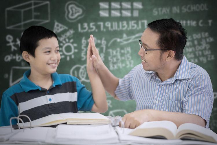 Boy with teacher at table against blackboard