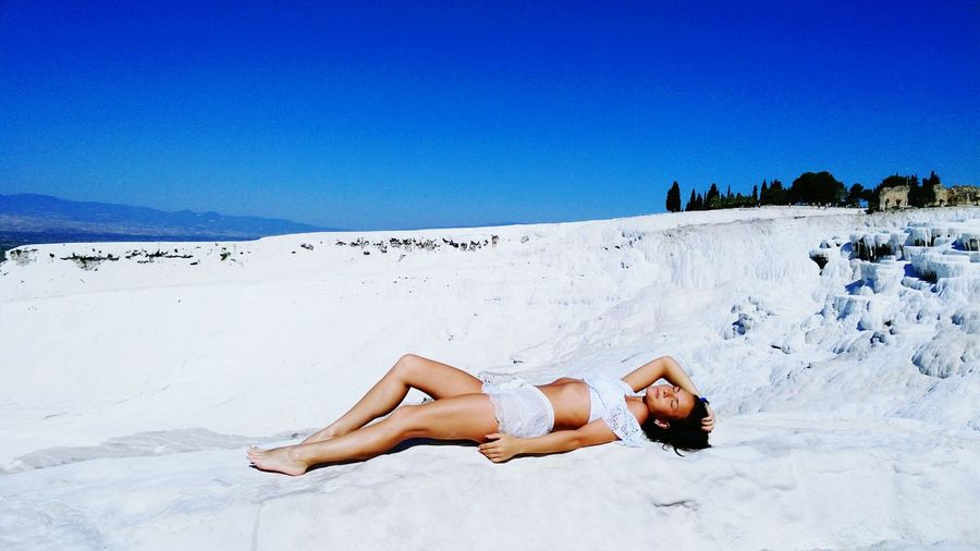 Young woman lying on white travertine terrace against clear blue sky