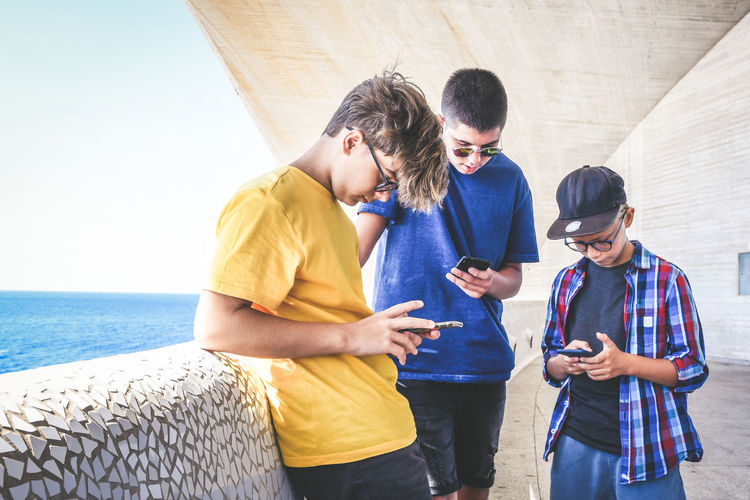 Friends using smart phones while standing by sea