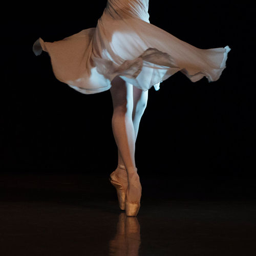 Low section of ballerina dancing against black background