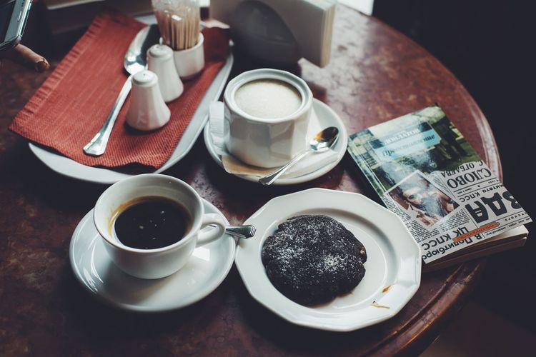 High Angle View Of Black Coffee With Milk And Cookie On Table