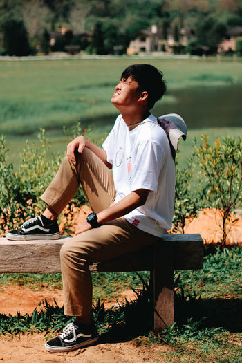 Young man looking at camera while sitting on land