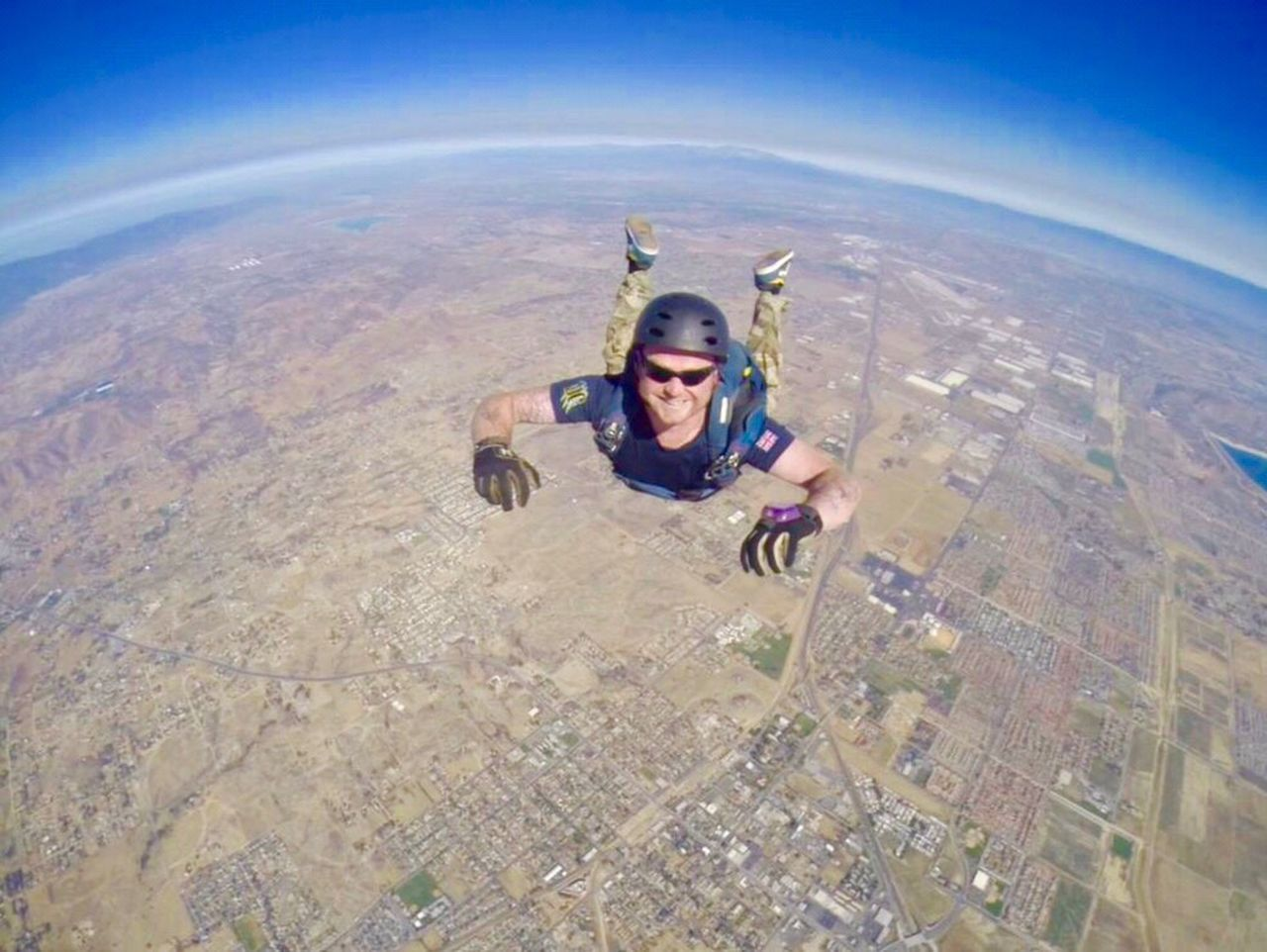 helmet, adventure, skydiving, fish-eye lens, fun, people, exhilaration, extreme sports, sports helmet, headwear, one person, looking at camera, full length, day, outdoors, smiling, leisure activity, excitement, aerial view, motion, portrait, human body part, happiness, sky, children only, adult, young adult