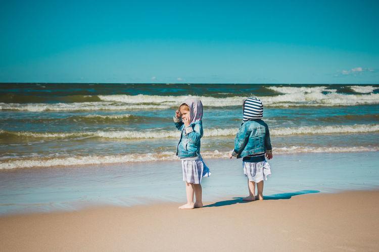 Full length of children on beach against sea