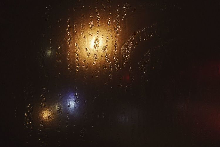 Raindrops on window against sky at night