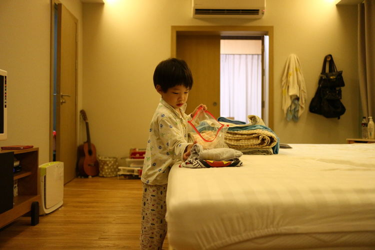 Side View Of Boy Standing In Bedroom At Home
