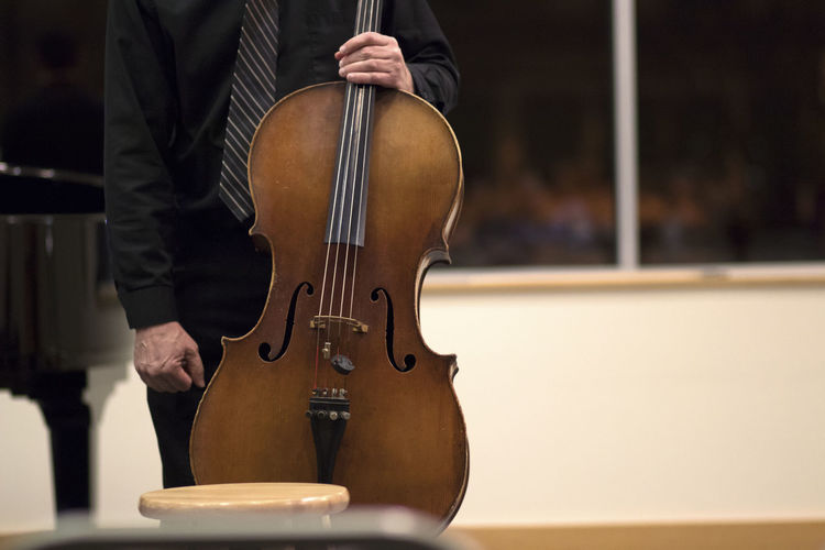 Midsection of man with cello during music concert