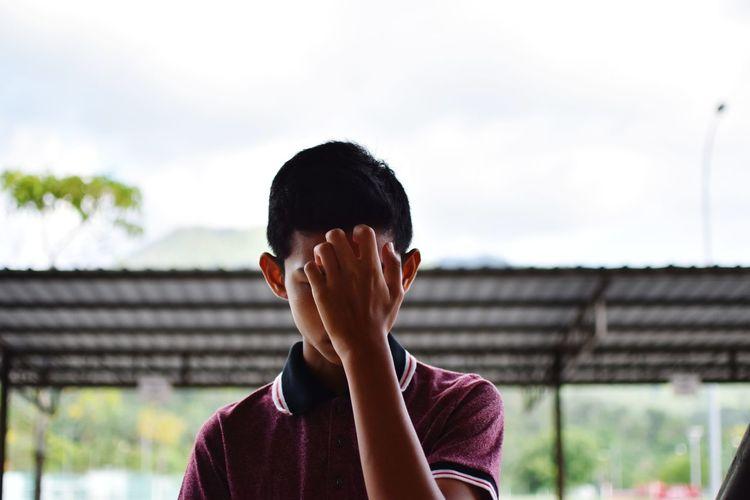 Close-up of man hiding face against sky