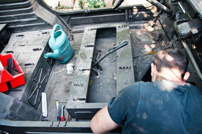 Rear View Of Mechanic Repairing Vehicle In Workshop