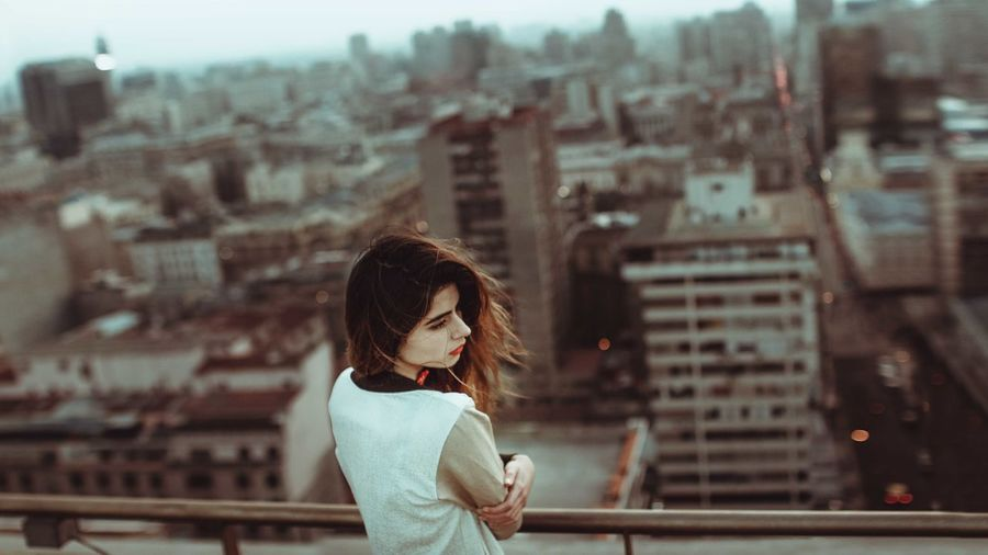 Woman looking at cityscape in city