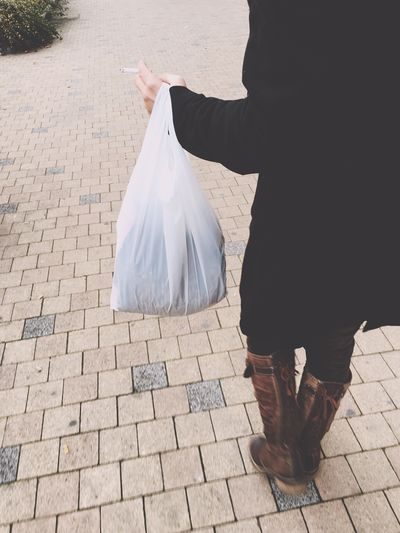 Low section of woman carrying plastic bag on footpath