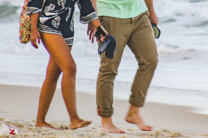 Low section of couple walking at beach