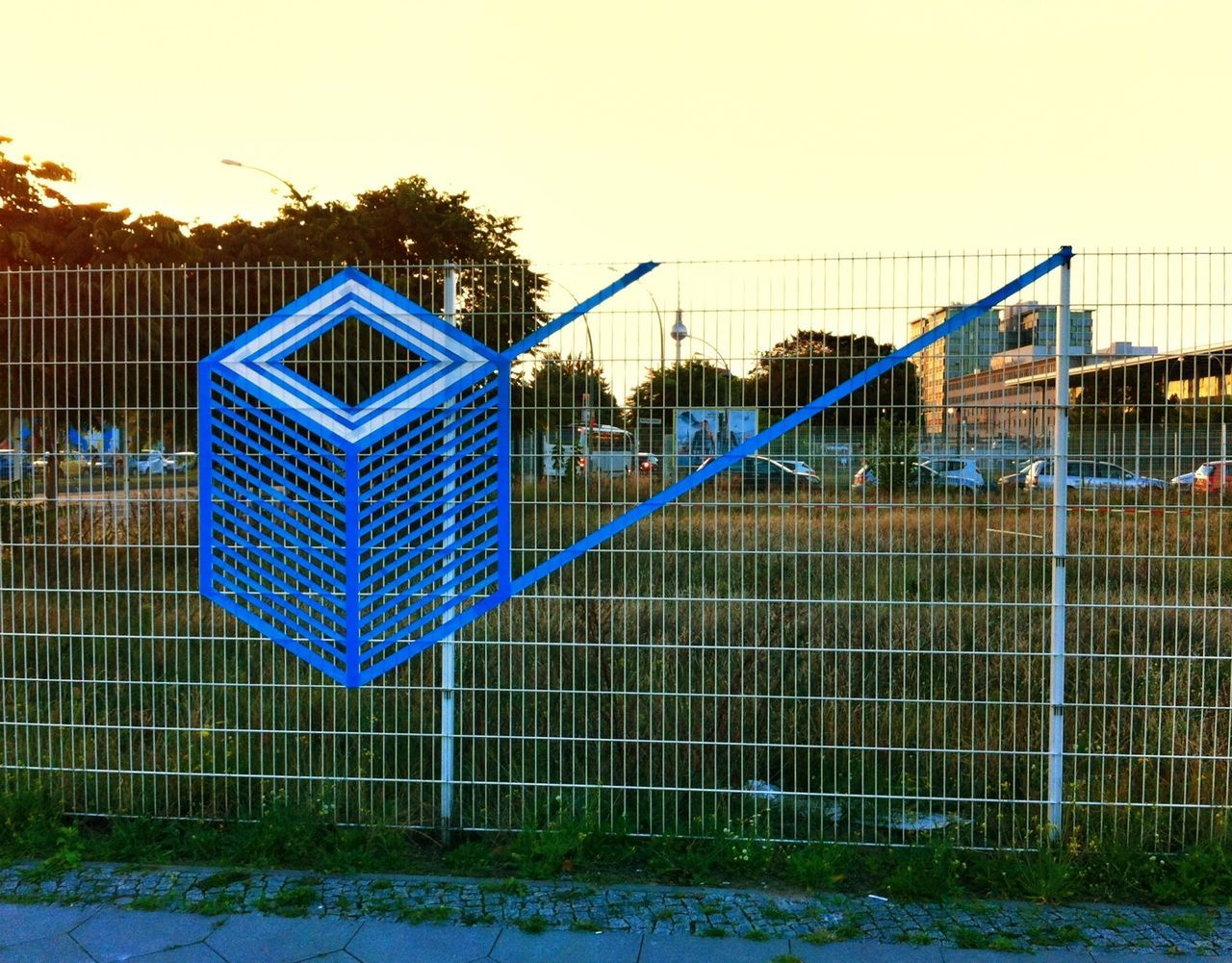 Tape art on fence in city against clear sky
