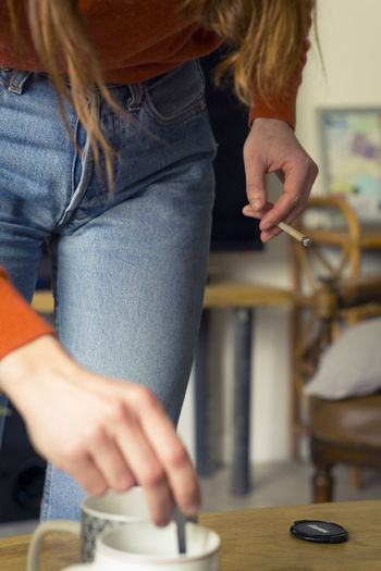 Womans legs, wearing a blue jean in the interior of a decorated house, holding a cigarettes. Cigarettes Coffee Fashion Smoke Smoking Adult Blue Cigarette  Close-up Day Holding Human Body Part Human Hand Indoors  Lifestyles One Person Orange Color People Real People Standing Women Young Adult Inner Power