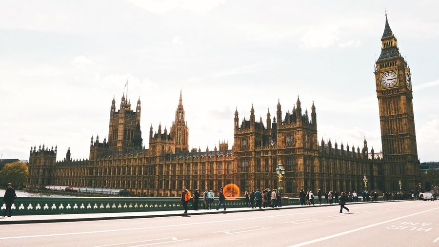 Westminster bridge by big ben against sky