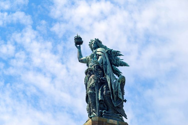 Bronze sculpture: Germania figure holding the crown of the emperor and the imperial sword - a part of the monument Niederwalddenkmal which represents the unification of Germany after the end of the Franco-Prussian War. Monuments Niederwalddenkmal Architecture Art And Craft Bronze Sculpture Cloud - Sky Craft Crown Royal Germania Germany History Human Representation Low Angle View Memorial Monument No People Outdoors Patina Representation Rüdesheim Am Rhein Sculpture Sky Statue The Past Unification