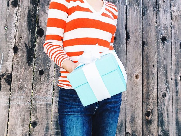 Midsection of woman holding gift box against wooden fence