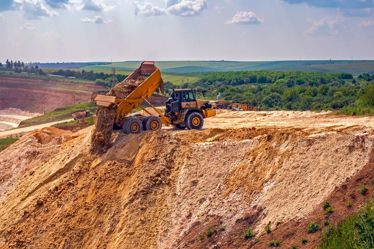 Kaolin quarry with white gypsum material and truck Agricultural Machinery Construction Machinery Construction Site Construction Vehicle Day Development Dump Truck Earth Mover Land Vehicle Landscape Machinery No People Outdoors Sky Transportation
