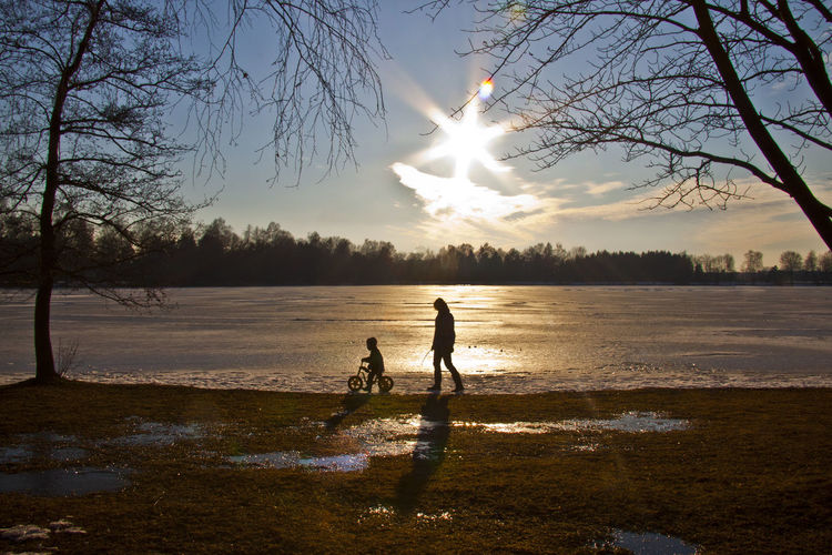 wandering in winter at lake Olching, Bavaria Bare Tree Bare Trees Beauty In Nature Boys Day Field Leisure Activity Lifestyles Mammal Nature Outdoors People Pets Real People Scenics Silhouette Sky Standing Sun Sunlight Sunset Togetherness Tree Two People Water