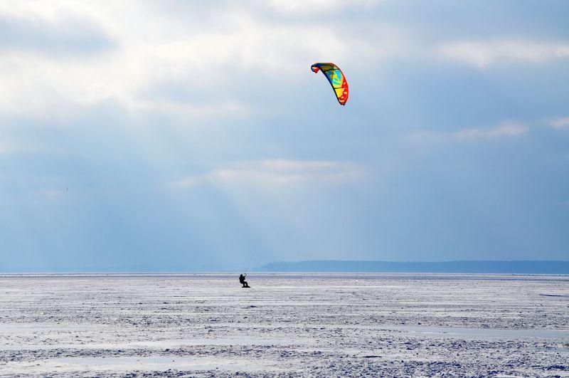 Person Kiteboarding In Sea Against Sky