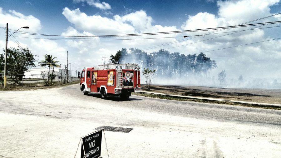 Fire engine van on road against cloudy sky