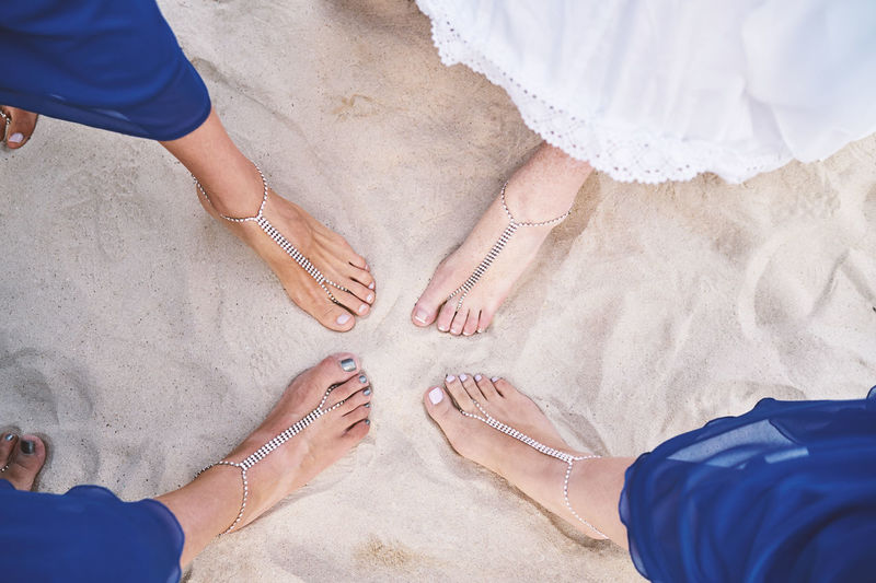 Bridal party play on the beach, Bride and bridesmaids show feet with bracelets on the sand Beach Wedding Beautiful Bohemia Bridesmaid Celebration Happiness Joyful Wedding Ankle Body Part Bracelet Bridal Party Bride Ceremony Friendship High Angle View Jewellery Jewelry Lifestyles Necklace Newlywed Party Playful White Sand Women