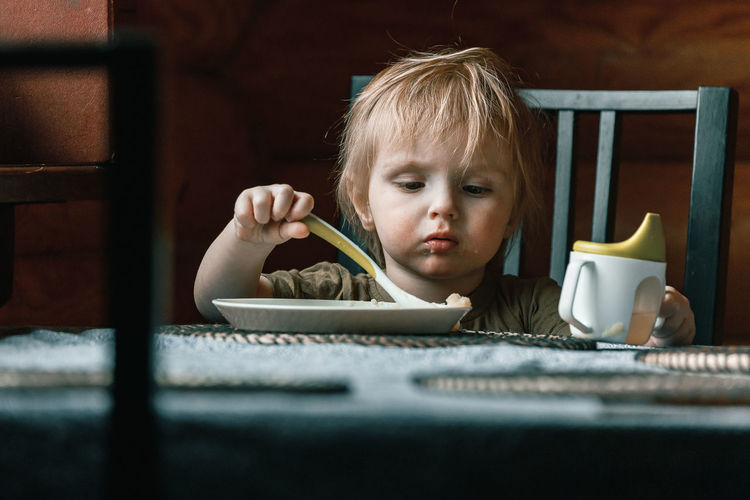 Portrait of boy holding coffee cup on table