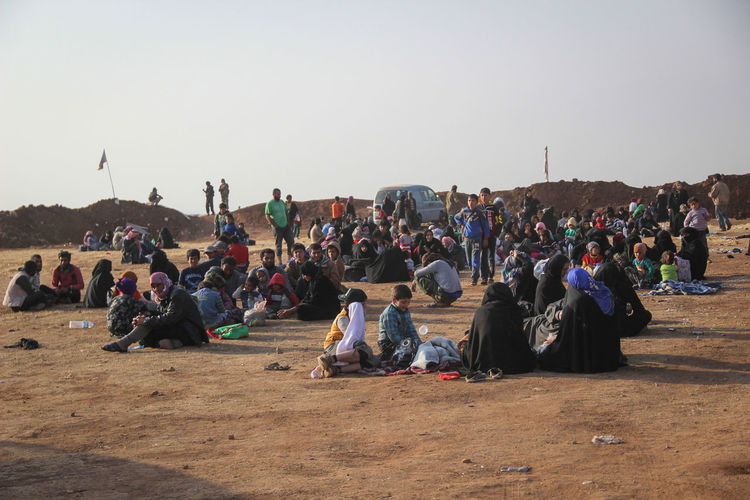 Group of people relaxing on land against clear sky