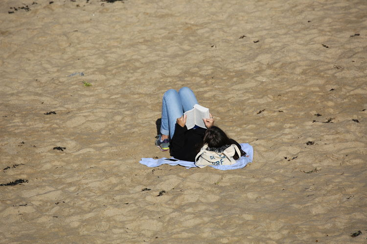 High angle view of woman reading book while resting at beach