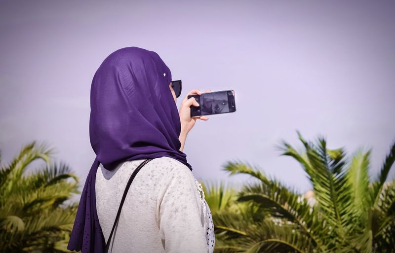 Rear view of young woman photographing with mobile phone against sky