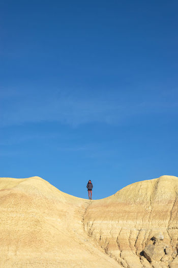 Rear view of man standing on desert against sky