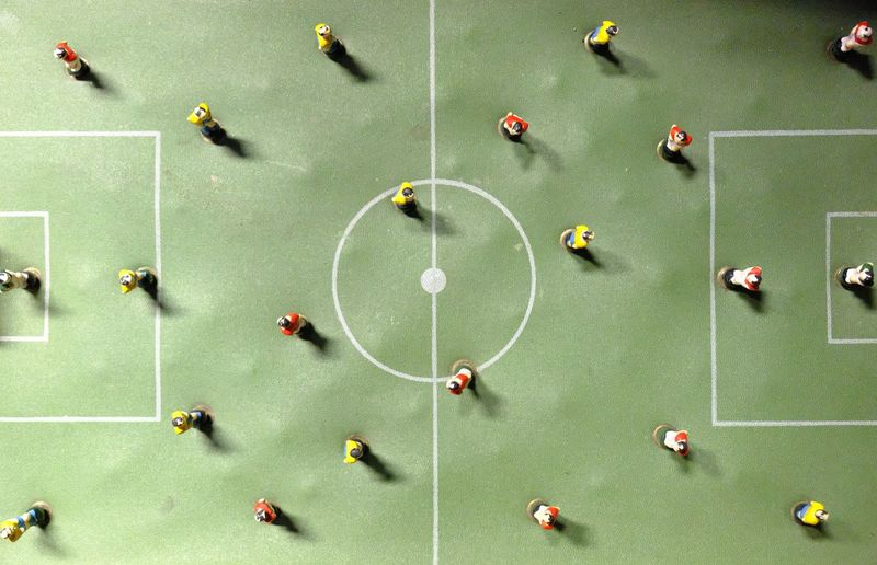 Directly above shot of figurines on artificial soccer field