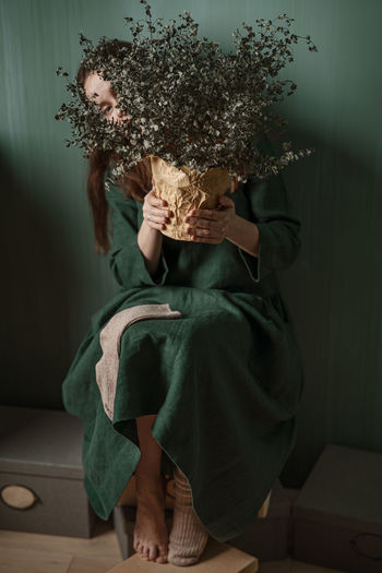 A young woman in a green linen dress making her creative self-portrait against a green wall