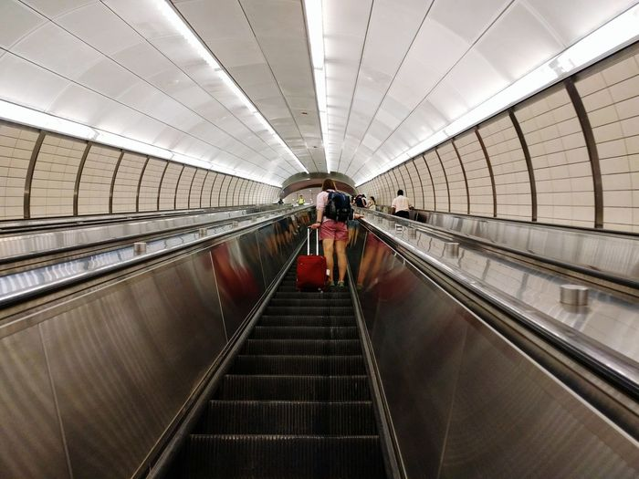 A tourist rides an escalator on the way to catch a bus. Escalator Movement Travel Upward Mobility Rise Female First Eyeem Photo Suitcase Tunnel Climb