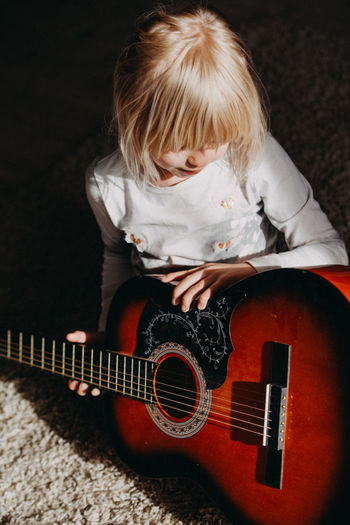 Girl Playing Guitar While Sitting At Home