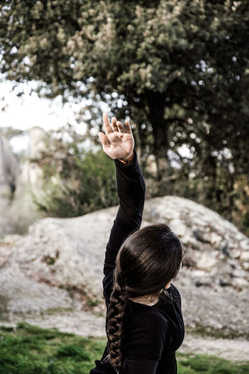 Side view of woman with arm raised exercising in park