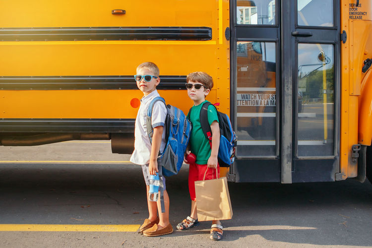 Full length portrait of boys while standing on road by bus