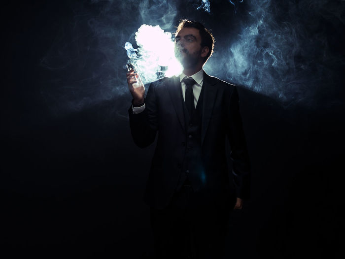 Man holding cigar while standing at night