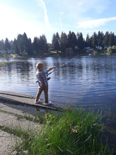 Boy fishing while standing at lakeshore