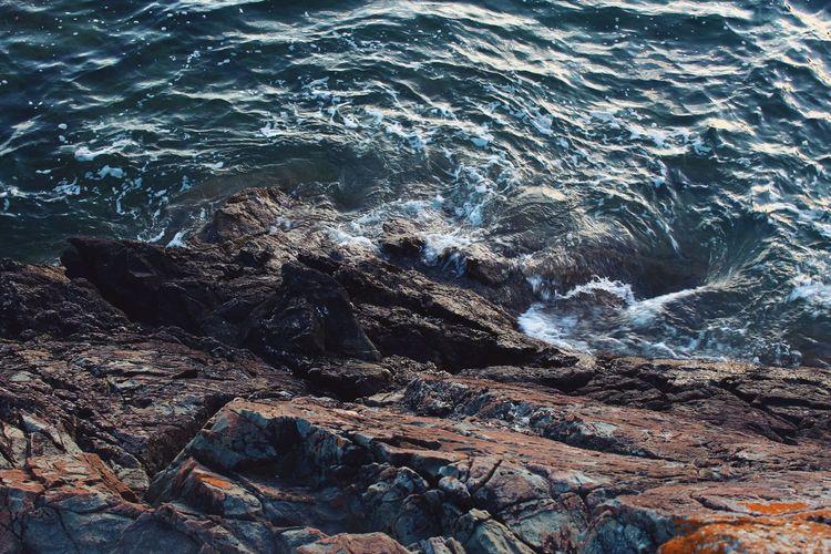 Scenic view of sea waves splashing on rock