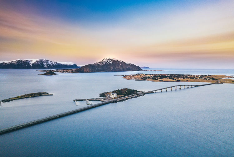 Amazing evening panorama in Norway with long bridge. Islands Norge Norway Alesund Beauty In Nature Beauty In Nature Bridge Bridge - Man Made Structure Cold Temperature Evening Fjord Idyllic Landscape Mountain Nature Northsea Scenics - Nature Sea Snowcapped Mountain Sunset Tranquility Village Water Waterfront Winter