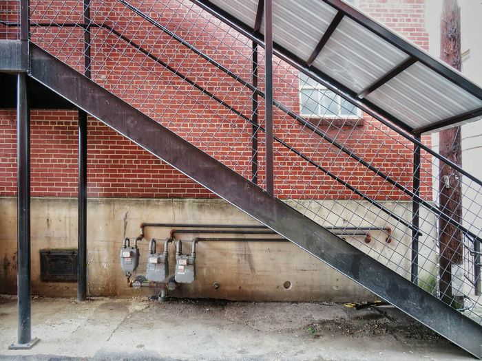 Metal staircase against exterior brick wall