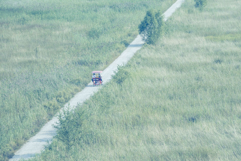 High Angle View Of People Riding Vehicle On Road Amidst Grassy Field