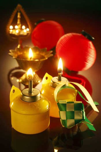 High Angle View Of Decoration And Illuminated Oil Lamp On Table