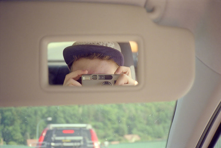 Man photographing through smart phone in car