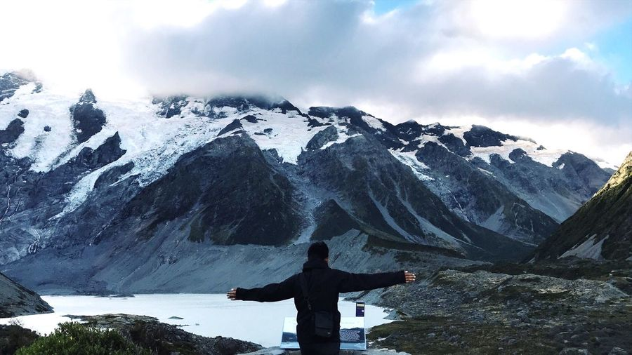 Rear View Of Man With Arms Outstretched Against Snowcapped Mountain