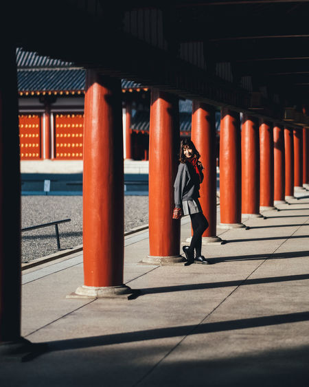 Full length of woman standing by columns in corridor